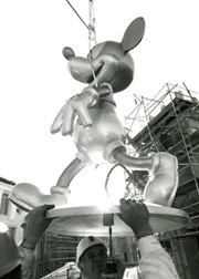 Mickey Mouse being hoisted onto the Crossroads tower at Walt Disney World in Orlando, Florida.