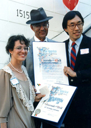 Councilman Michael Woo presents Owner Mort La Kretz and his daughter Margaret with the City of Los Angeles' recognition of Crossroads' 50th anniversary
